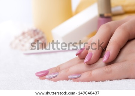 Manicure - very nice pink nail polish with glitter silver details on fingernails. Selective focus.