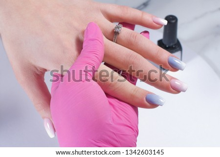Manicured hand with nail polish in pink and blue shades held by the hand of a manicurist in a pink hygienic glove. #1342603145