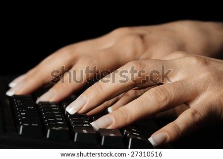 Manicured hands typing on black keyboard selective focus