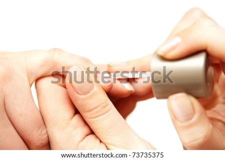 Manicurist applying nail polish on female fingers
