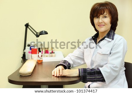 Manicurist dressed in white robe sits at table for manicure in beauty salon