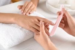Manicurist filing client's nails at table, closeup. Spa treatment