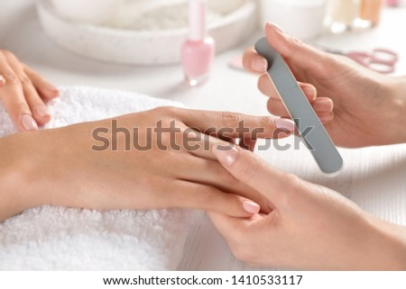 Manicurist filing client's nails at table, closeup. Spa treatment Stok fotoğraf ©