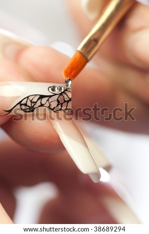 Manicurist treating client at beauty salon. Manicure stage: gluing crystals on nail
