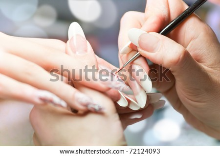 Manicurist treating client at beauty salon. Manicure stage: Painting on the nail