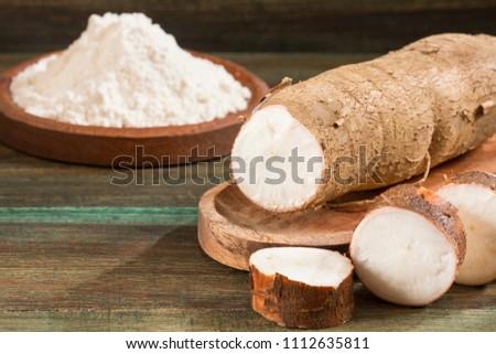 Manihot esculenta (cassava, yuca, manioc, mandioca, Brazilian arrowroot) and tapioca on wooden background. Selective focus #1112635811