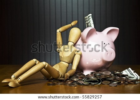 Manikin leaning against a piggy bank surrounded by money