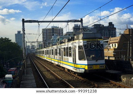 MANILA - APRIL 02: LRT train arrives at a train station on April 02, 2012 in Manila, Philippines. LRT serves 579,000 passengers each day. Its 31 stations along over 31 kilometers (19 mi) .