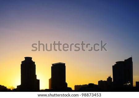 Manila buildings silhouetted against sunrise