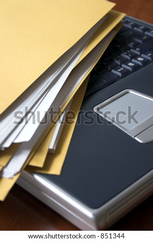 Manila folder stuffed with papers on top of a laptop
