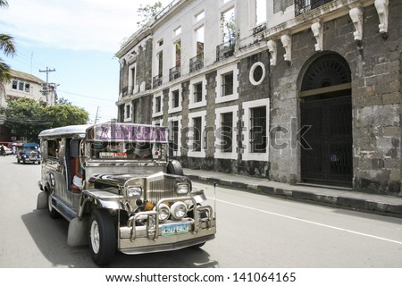 MANILA - JULY 10: jeepney public transport driving past derelict building in intramuros on 10 July 2009 in manila. Jeepneys are the most popular means of public transportation in the Philippines.
