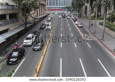 Manila, Philippines - March 6, 2018: Cars  going along the road in center of Makati #1040228392
