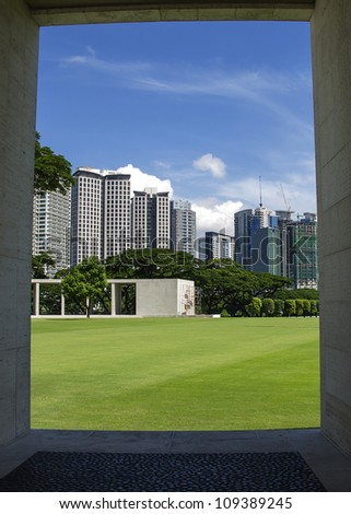 Manila skyline, framed by the monument at the city's American war cemetery.