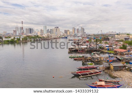 Manila slums on the background of a big city. Houses and boats of the poor inhabitants of Manila. Dwelling poor in the Philippines. Contrast social strata.