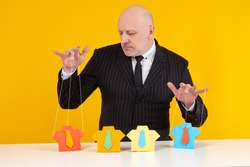 Manipulating people. Man controls paper men. He manipulates them like puppets. Concept - a businessman manipulates staff. Portrait of a recruiter on a yellow background. Puppeteer manipulator