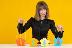 Manipulation of people concept. Woman is manipulating someone. She manipulates paper men like a puppeteer. Portrait of a woman puppeteer on a yellow background. Puppeteer manipulates people