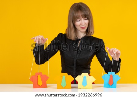 Manipulation of people concept. Woman is manipulating someone. She manipulates paper men like a puppeteer. Portrait of a woman puppeteer on a yellow background. Puppeteer manipulates people Foto stock ©