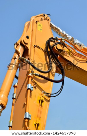 Manipulator crane with hydraulic cylinder. Working equipment of logging equipment. Close-up of the crane fragment. Against the blue sky.