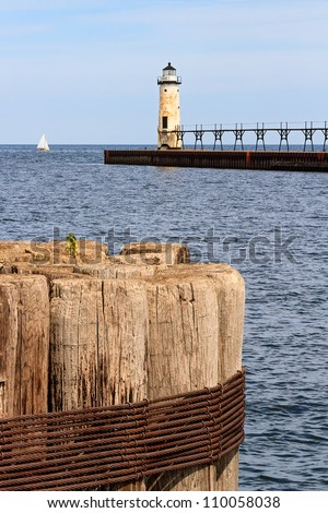 Manistee North Pierhead Lighthouse on Lake Michigan with wood timber piling and sailboat on the horizon.