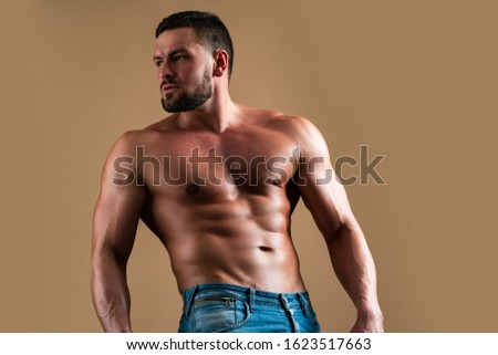 Manly body. Perfect mans body. Muscular man on beige background. Ab and biceps