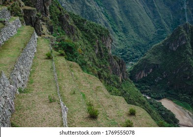 Stock photo of manmade stone wall structures. There is a mountain in the background. The sky is cloudy.