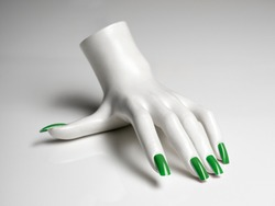 mannequin hand with perfect manicure and green nail polish