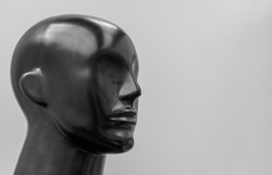 Mannequin made of black plastic. Mannequin head close-up, half-face view. Smooth contours without details. Glare.