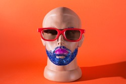 Mannequin male head in red glasses with blue glitter beard and eyebrowns and pink lipstick. Male gay makeup concept
