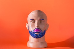 Mannequin male head with blue glitter beard and eyebrowns and pink lipstick. Male gay makeup concept