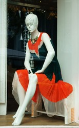 Mannequin wear stylish clothes and necklace showed on shopwindow of fashion shop
