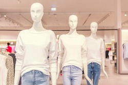 Mannequins in jeans and white sweaters in a clothing store during sales. Space for text.