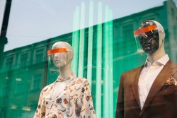 Mannequins in showcase of luxury brands shop  wearing masks against coronavirus during coven-19 pandemic. Trends of fashion and lifestyle in spring 2020. Empty streets of big city. Online shopping .