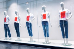 Mannequins on a shop window in a shopping center in mocap undershirts and jeans. Sell-out.