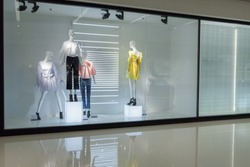mannequins with dress in fashion store display window