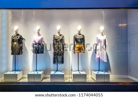 mannequins with modern clothes in fashion store display window