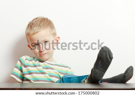 Manners. Portrait of bored naughty boy child preschooler making sulky moody face. Kid with feet on the table. At home. Foto stock ©