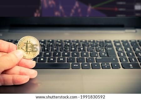 mano che tiene una moneta Bitcoin dorata su un computer portatile per analizzare il mercato delle criptovalute. Criptovaluta BTC. Valuta digitale. Foto d'archivio ©