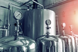 Manometers on steel cylinder storages or vats or tanks on juice and water production plant, industry machine equipment, blue toned
