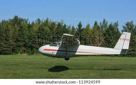 MANOTICK, CANADA - AUGUST 19: A special glider, used to train pilots, landing at Rideau Valley Soaring on August 19, 2012 in Manotick, Ontario. The club also offers flights to the public.