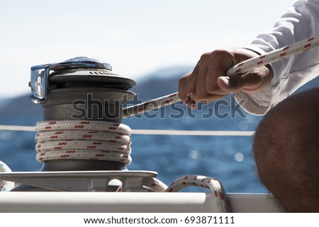 Mans hand pulling winch rope on sailing boat