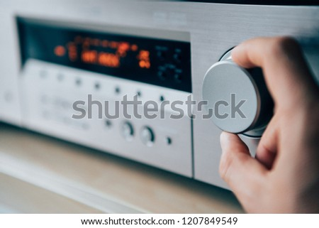 Mans hand rotating the Amplifier Volume regulator Adjusting the loudness  #1207849549