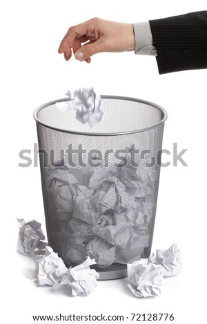 Mans hand throwing crumpled paper into a silver wire mesh trash bin