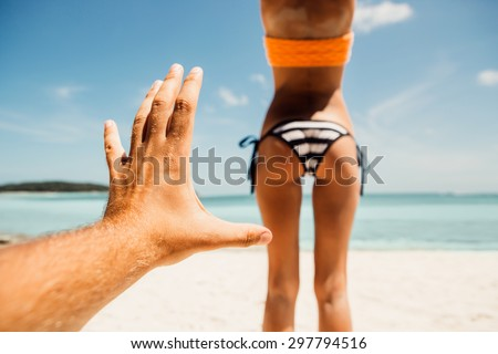 Mans hand trying to touch tanned fit ass of a sporty young beautiful woman in a sexy stripped bikini on a ocean shore background. Outdoor lifestyle picture on a hot sunny summer day. #297794516