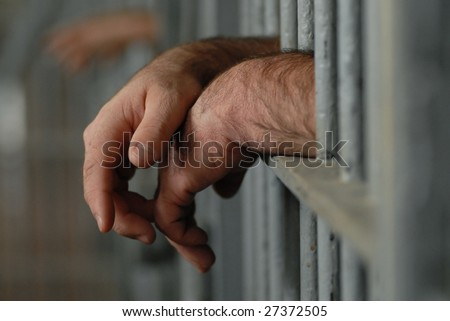 mans hands behind bars in jail or prison