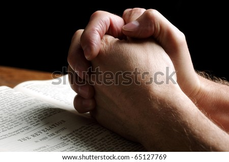 Mans hands folded in prayer over an open Holy Bible