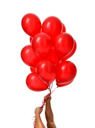 Mans hands hold bunch of big red balloons object for birthday party isolated on a white background