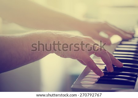 Mans hands playing piano selective focus