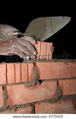 Mans hands with a trowel and laying a brick