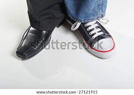 Mans legs wearing jeans and sneaker on a leg and suit on other - stock photo