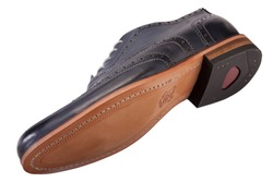 mans shoe detail showing the leather sole from below as well as the upper